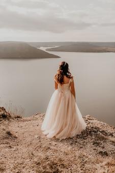 Bella giovane sposa bruna in un abito da sposa bianco con una corona in testa si trova su una scogliera sullo sfondo del fiume e delle isole