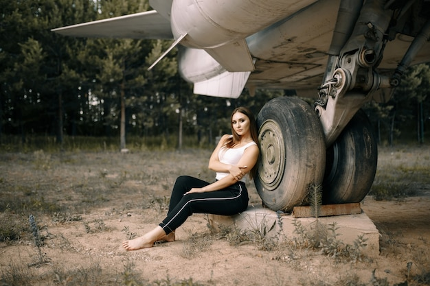 Bella giovane ragazza bruna si leva in piedi sullo sfondo di vecchi aerei militari.