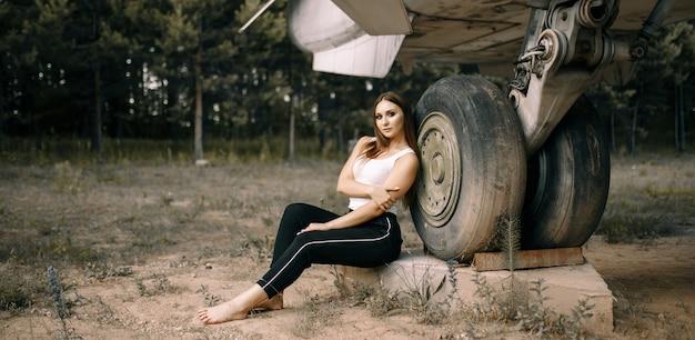 Bella giovane ragazza castana si leva in piedi sullo spazio di vecchi aerei militari