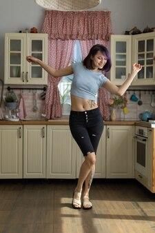 La bella giovane ragazza castana in una maglietta e calzoni balla e beve il caffè da una tazza nella cucina a casa