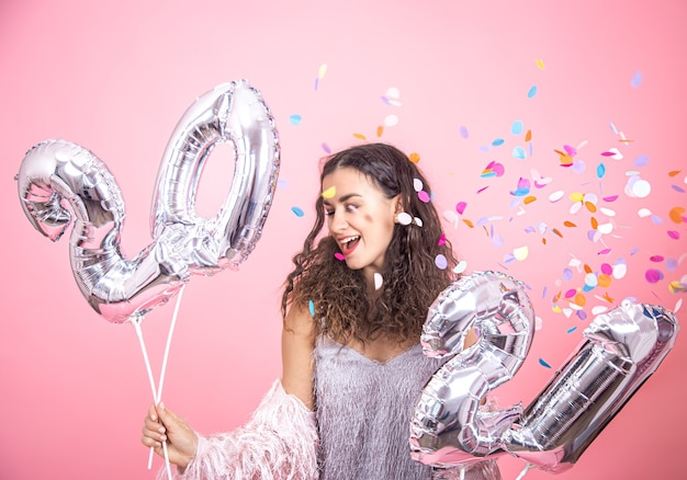 Bella giovane ragazza castana con capelli ricci in posa su una parete rosa con coriandoli e tenendo in mano palloncini d'argento per il concetto di nuovo anno