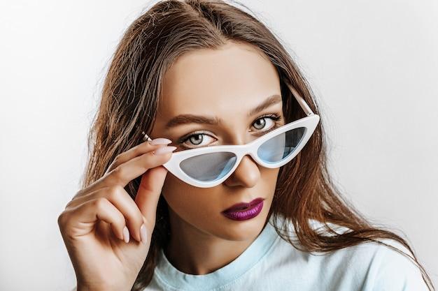 Bella giovane ragazza bruna con gli occhi verdi con il trucco di moda con le labbra viola