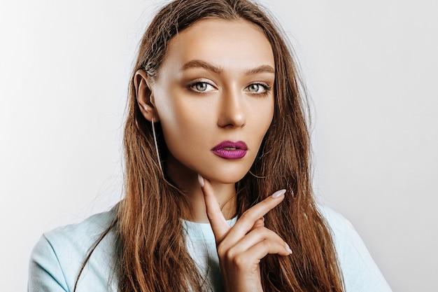 Bella giovane ragazza castana con gli occhi verdi con capelli lunghi con il trucco di modo con le labbra viola su un muro grigio isolato. la donna tiene la mano in faccia e guarda seriamente la telecamera
