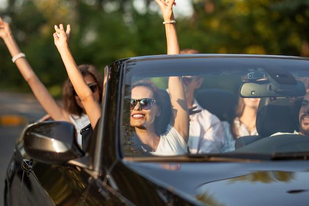 La bella giovane signora castana in occhiali da sole si siede con gli amici in un cabriolet nero sorride e alzando le mani in una giornata di sole. .