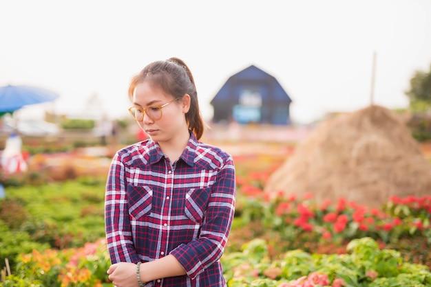 Bella giovane donna bruna sul prato con fiori bianchi in una calda giornata estiva - immagine