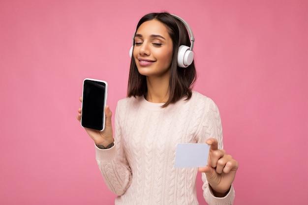 Bella giovane donna bruna che indossa un maglione casual rosa isolato su sfondo rosa wall