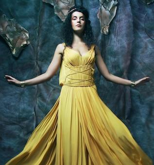 Bella giovane donna bruna che indossa abito da sera giallo yellow