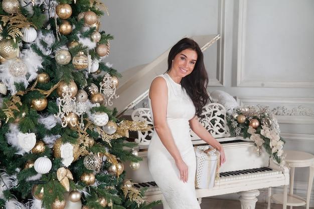 Bella giovane donna castana in abito da cocktail da sera bianco in posa con un pianoforte bianco e albero di natale decorato con regali in interni di lusso classici.