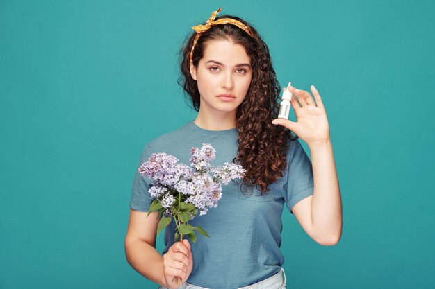 Bella giovane donna castana con il mazzo di lillà fiorito che mostra lo spray antiallergico per il naso che usa per curare l'allergia ai pollini