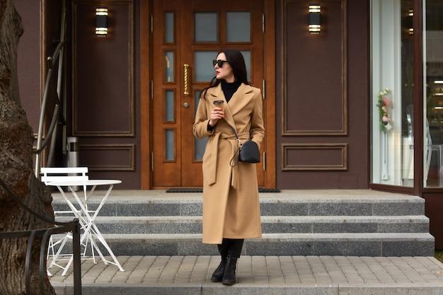 Bella giovane donna del brunettee in cappotto beige moderno, tenendo tazza da asporto usa e getta e in piedi contro l'edificio urbano della città
