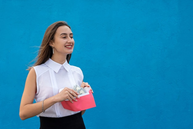 Bella giovane donna d'affari in possesso di una busta con dollari su sfondo blu. concetto di corruzione, stipendio in busta o shopping