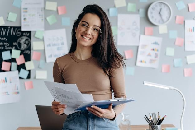 Bella, giovane donna d'affari tiene in mano documenti importanti Foto Premium