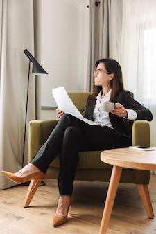Bella giovane donna d'affari in abiti formali al chiuso a casa a bere caffè lavorare con i documenti.