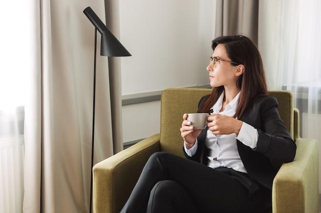 Bella giovane donna d'affari in abiti da cerimonia al chiuso a casa a bere caffè.