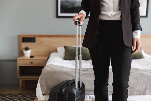 Bella giovane donna d'affari in abiti da cerimonia al chiuso a casa con la valigia.
