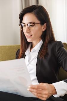 Bella giovane donna d'affari in abiti da cerimonia al chiuso a casa lavora con documenti e grafica.
