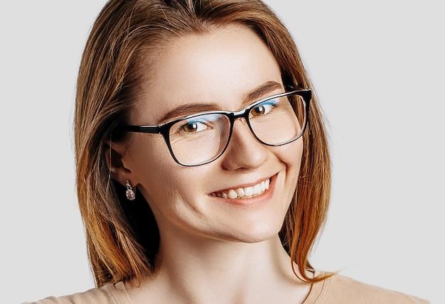Bella giovane donna d'affari sorride con gli occhiali isolati su sfondo grigio. raggiungere il concetto di business ricchezza di carriera.