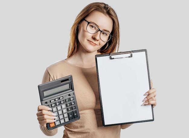 Bella giovane donna d'affari con gli occhiali tiene calcolatrice e appunti con mock up spazio vuoto isolato su uno spazio grigio