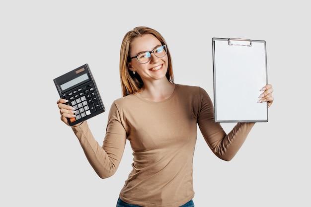 Bella giovane donna d'affari con gli occhiali tiene calcolatrice e appunti con finto spazio vuoto isolato su superficie grigia
