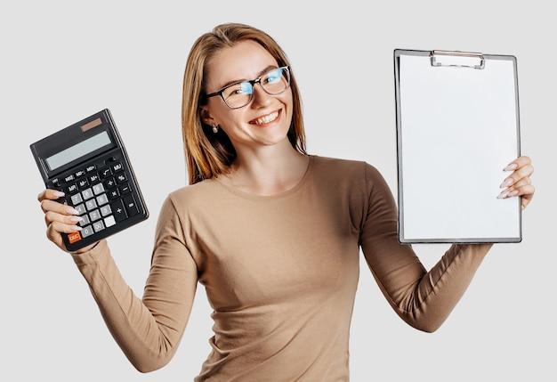 La bella giovane donna di affari che indossa gli occhiali tiene la calcolatrice e la lavagna per appunti