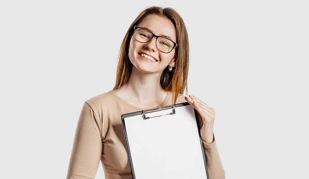 La bella giovane donna di affari che indossa gli occhiali tiene una lavagna per appunti con uno spazio vuoto mock up isolato su spazio grigio