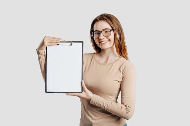 La bella giovane donna di affari che indossa gli occhiali tiene i appunti