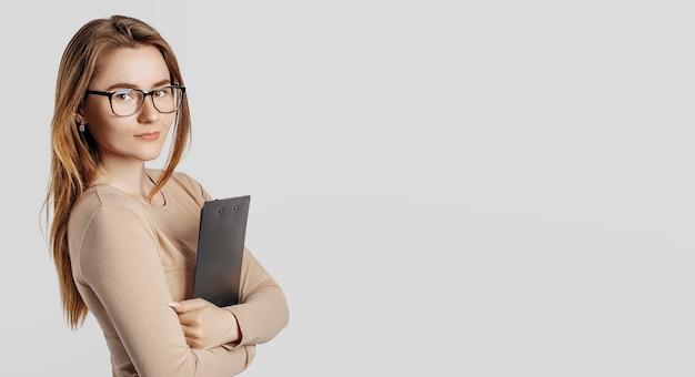 Bella giovane donna d'affari con gli occhiali isolati su uno spazio grigio