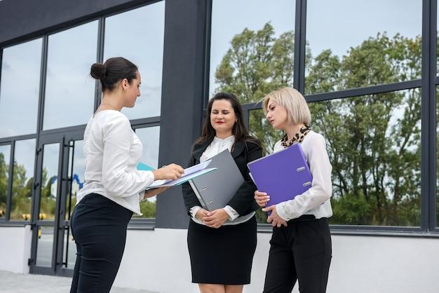 Belle e giovani donne d'affari con documenti e cartelle in posa fuori dall'edificio degli uffici