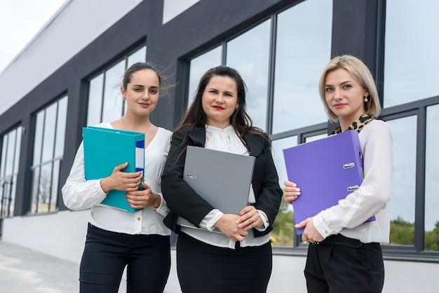 Belle e giovani donne d'affari con documenti e cartelle in posa all'esterno dell'edificio per uffici