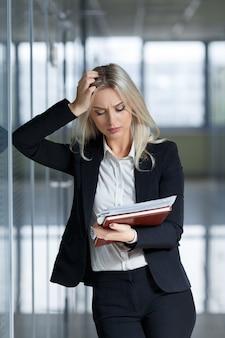 Bella giovane donna di affari arrabbiata e alla ricerca di documenti in ufficio.
