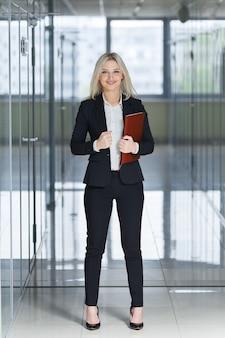 Bella giovane donna d'affari sorridente e in piedi con la cartella in ufficio