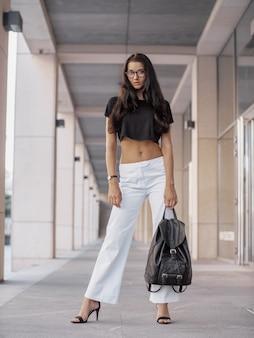 Bella giovane imprenditrice in piedi nella via della città. signora di moda affari alla moda in bicchieri guardando la telecamera in posa all'aperto