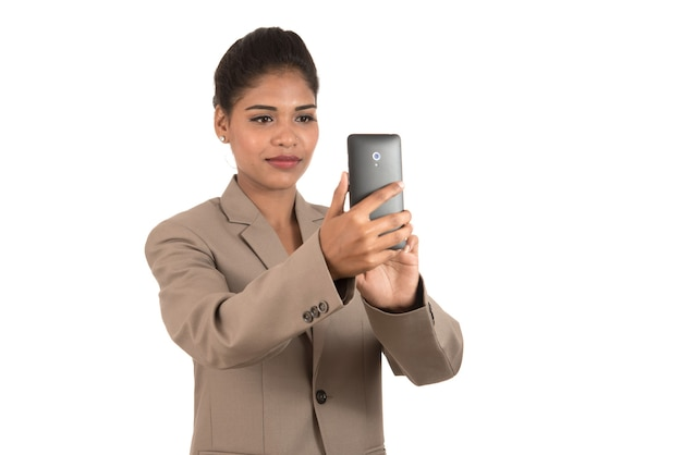 Bella giovane imprenditrice utilizza lo smartphone per scattare foto selfie isolato su sfondo bianco