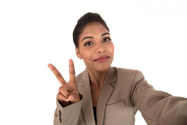 Bella giovane donna di affari che per mezzo dello smartphone per prendere la foto del selfie isolata su spazio bianco