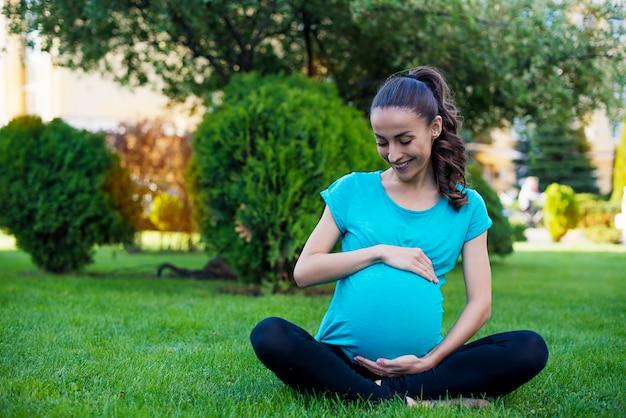 Bella giovane donna incinta calma è seduta nella posizione del loto e medita mentre pratica yoga nel parco