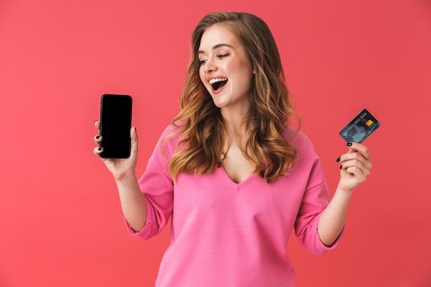 Bella giovane ragazza bionda casual in piedi isolata sul muro rosa, mostrando carta di credito in plastica e telefono cellulare