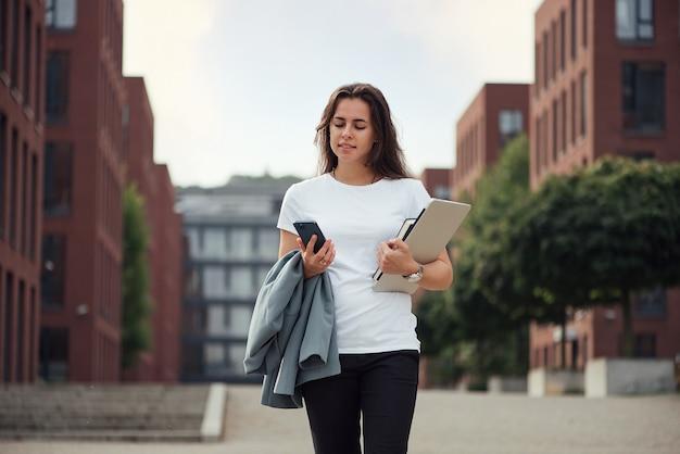 Bella giovane donna di affari caucasica con un computer portatile e un taccuino all'aperto facendo uso dello smartphone vicino