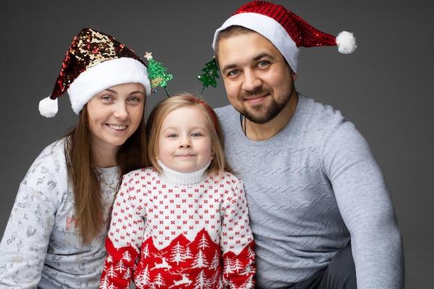 Una bella giovane famiglia caucasica di tre trascorre insieme il tempo di natale