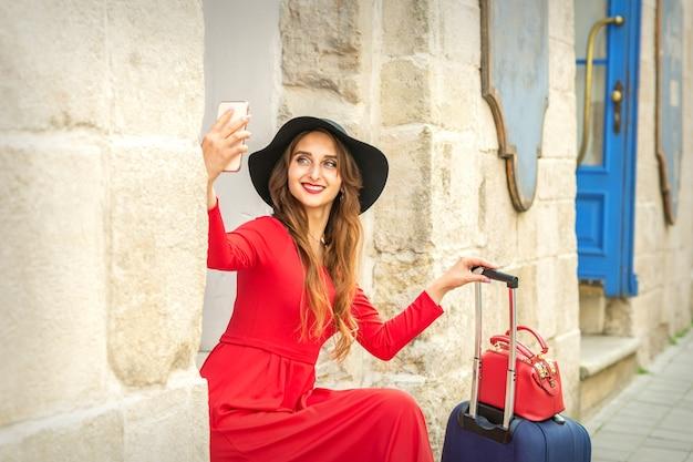 Bella giovane donna caucasica con cappello nero che guarda sullo smartphone sorridendo e seduta sulle scale