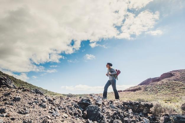 Bella giovane donna caucasica escursione e fare attività di trekking in montagna godendo la libertà attività di svago all'aperto da sola esplorando il mondo - concetto di stile di vita sano viaggio e avventura