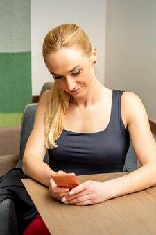 Bella giovane donna caucasica guardando smartphone seduto al tavolo in un caffè
