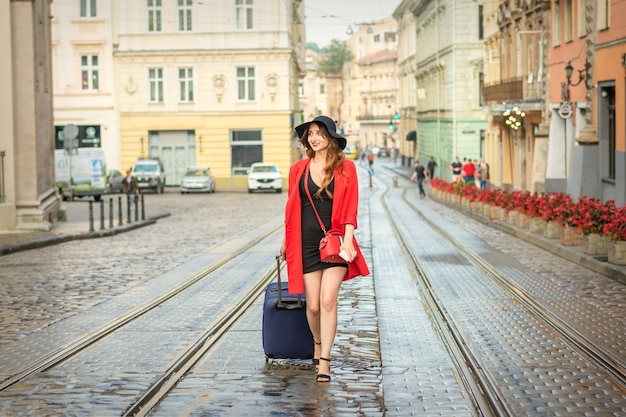 La bella giovane donna caucasica cammina con una valigia su una pista bagnata del tram nella città europea