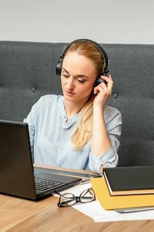 Bella giovane donna caucasica con cuffie e laptop seduto al tavolo in un caffè