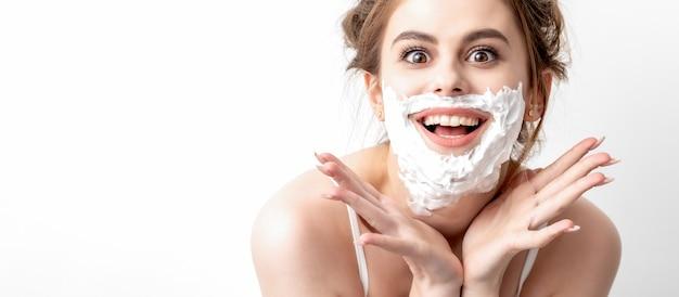 Bella giovane donna caucasica con schiuma da barba sul viso in posa sul muro bianco