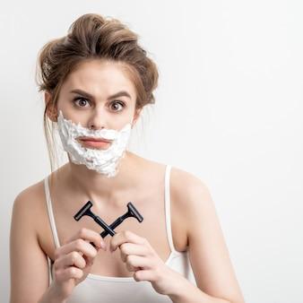 Bella giovane donna caucasica con schiuma da barba sul viso e due rasoi in mano sul muro bianco