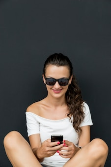 Bella giovane donna caucasica con smartphone, sms. adolescente felice con i capelli castani.