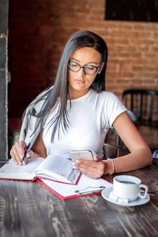 Bella giovane donna caucasica scrive note al blocco note che tiene smartphone in mano con gli occhiali nella caffetteria