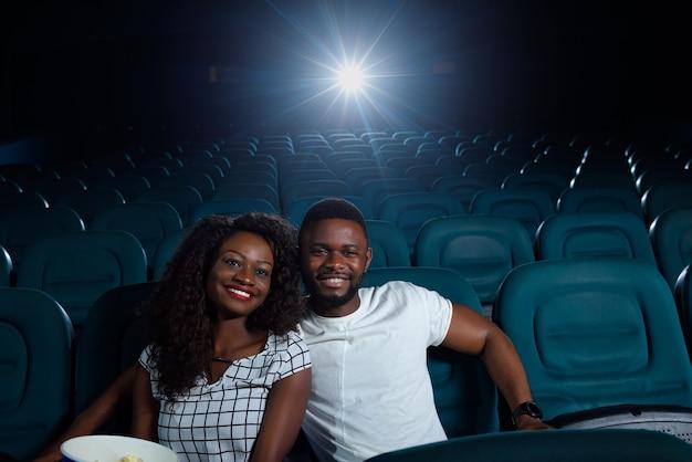 Bella giovane donna africana allegra che sorride felicemente mentre guarda un film con il suo ragazzo al cinema locale