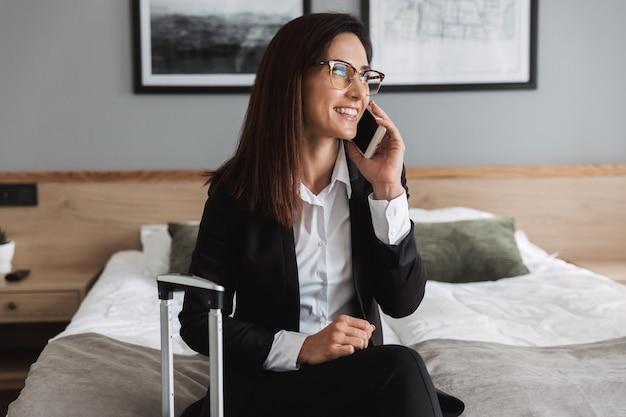 Bella giovane allegra felice donna d'affari in abiti formali al chiuso a casa con la valigia che parla al telefono cellulare.