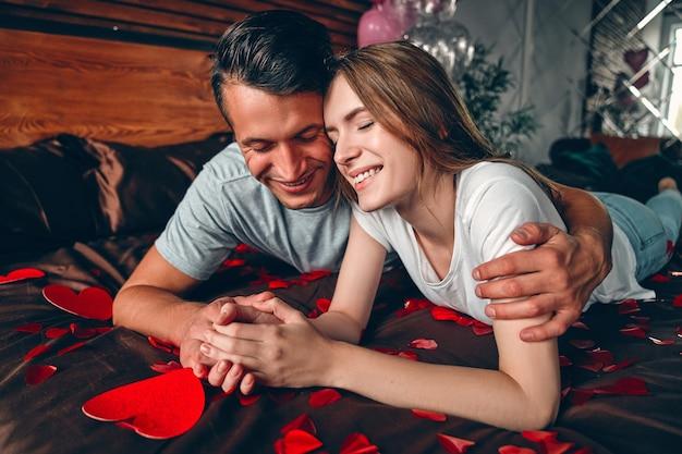 Bella giovane coppia in camera da letto è sdraiata sul letto e abbraccia